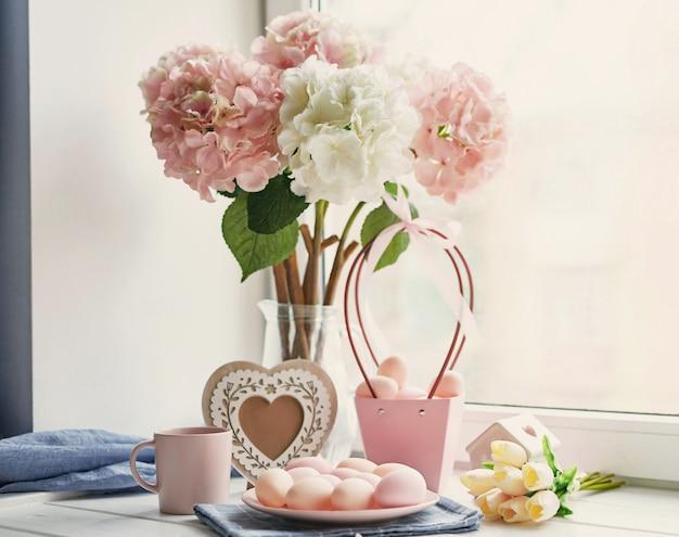 Composición de pascua con hortensias rosas y blancas en florero, tulipanes amarillos y huevos rosados