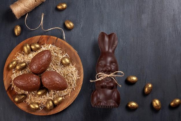 Composición de pascua con huevos de chocolate y conejito sobre fondo de madera