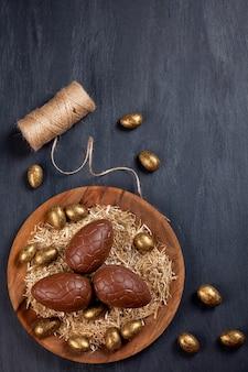 Composición de pascua con huevos de chocolate sobre fondo de madera de color