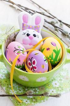 Composición de pascua con huevos de colores y conejo.