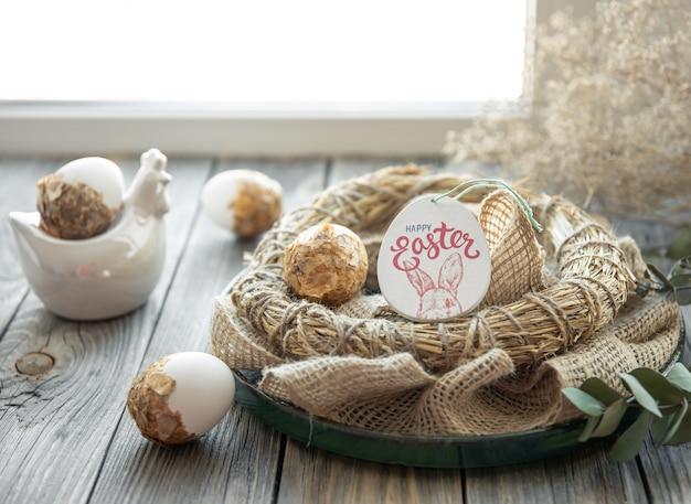 Composición de pascua con huevos de pascua decorados y nido decorativo sobre una superficie de madera