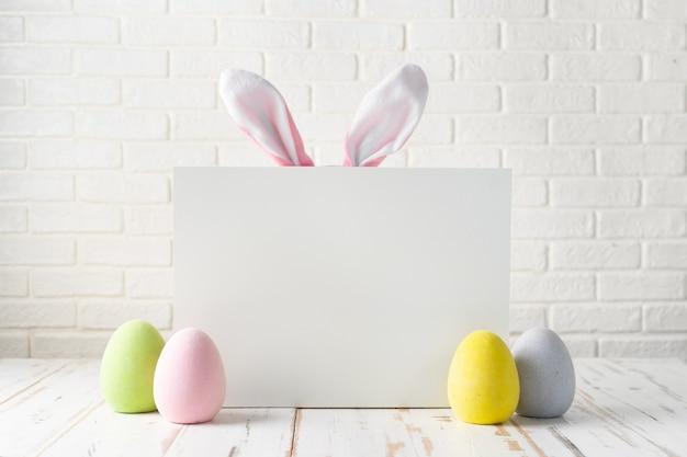 Composición de pascua con huevos, pizarra y orejas de conejo.