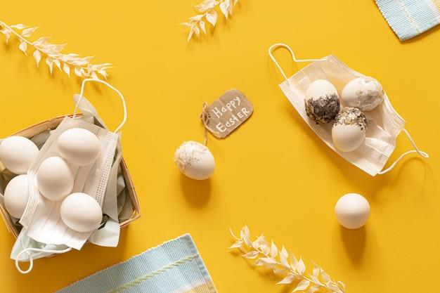 Composición de pascua de primavera con máscaras protectoras y vista superior de huevos de pascua dispersos.