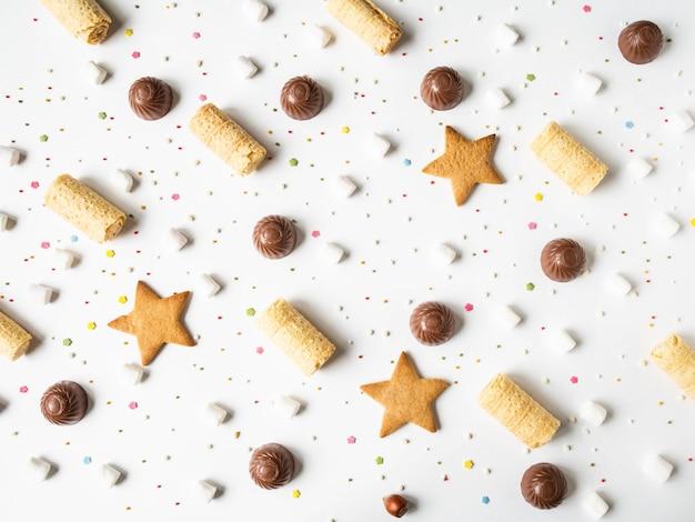 Composición de pastelería festiva dulce con chocolate, waffles, galletas, malvaviscos y pastelería topping sobre un fondo blanco.