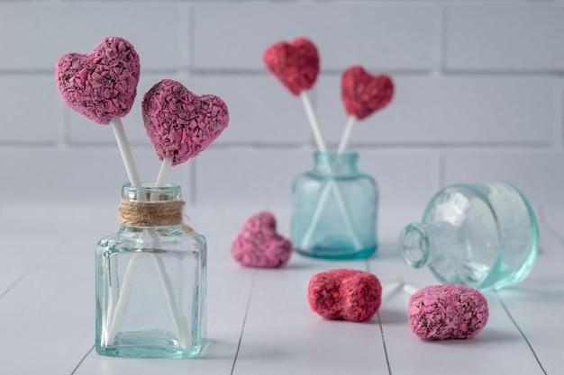 Composición con picaduras de energía en forma de corazón para el día de san valentín en la mesa de madera blanca
