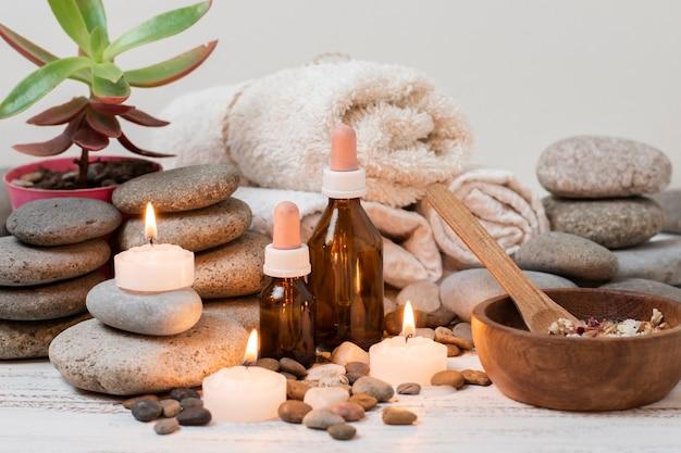 Composición con piedras de spa, velas encendidas y toallas.