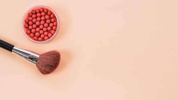 Composición de pincel de maquillaje y colorete sobre fondo claro