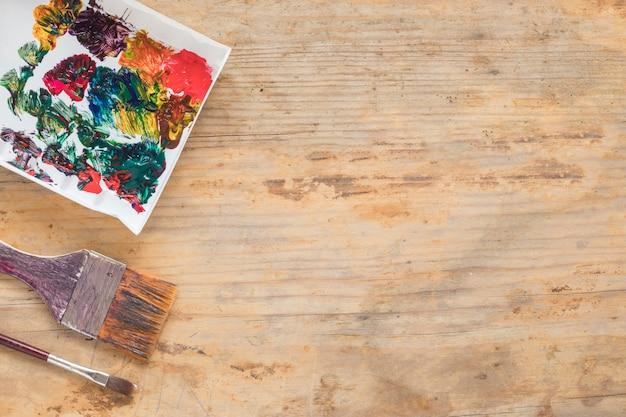 Composición de pinceles sucios y papel pintado.