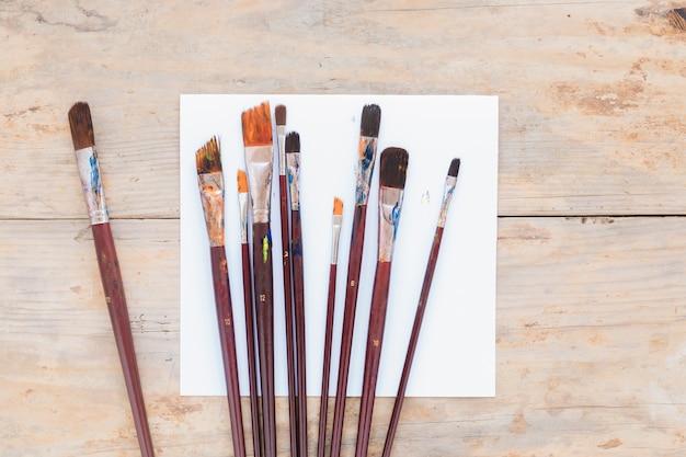 Composición de pinceles usados sobre papel blanco.