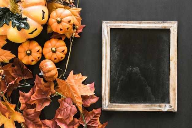 Composición de pizarra de halloween con hojas y calabazas
