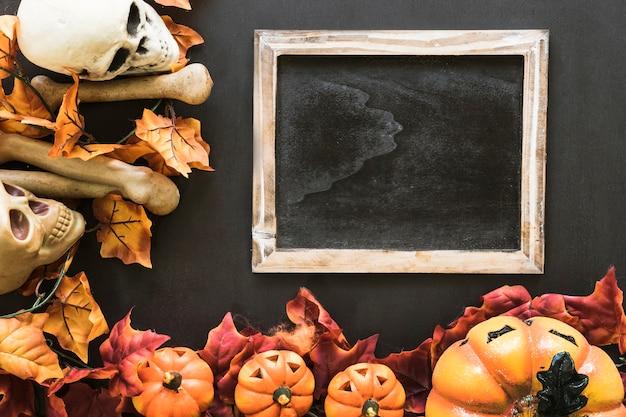 Composición de pizarra de halloween con hojas de otoño y huesos