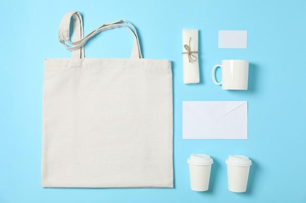 Composición plana con bolsa de algodón, vasos de papel y material de oficina sobre fondo azul.