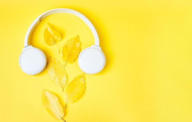 Composición plana de caída con hojas realistas y auriculares blancos sobre fondo amarillo. fondo de podcast de otoño. concepto de lista de reproducción de otoño. copia espacio
