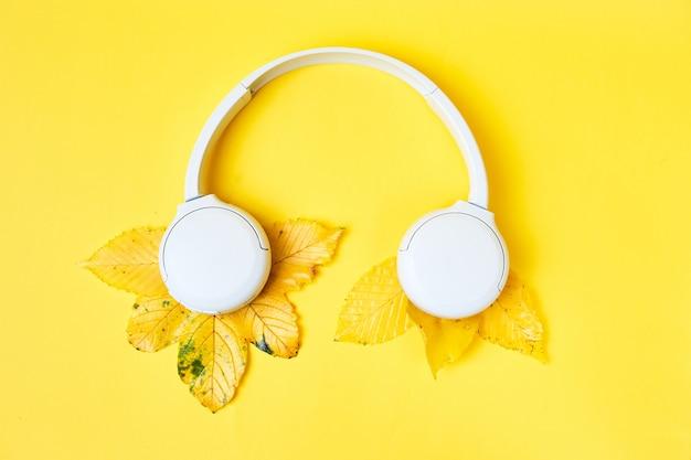 Composición plana de caída con hojas realistas y auriculares blancos sobre fondo amarillo. fondo de podcast de otoño. concepto de lista de reproducción de otoño.