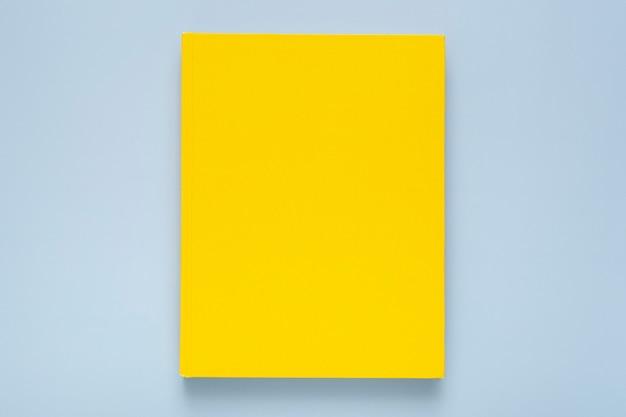 Composición plana con cuaderno amarillo sobre fondo azul.