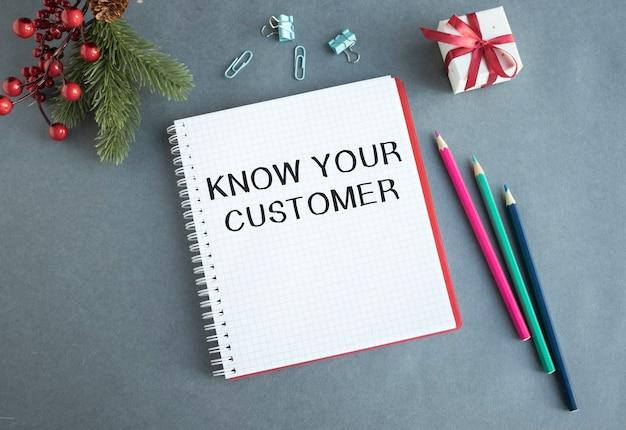Composición plana con cuaderno y texto conozca a sus clientes en la mesa de la oficina