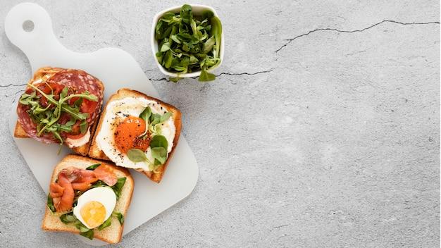 Composición plana de deliciosos sándwiches con espacio de copia