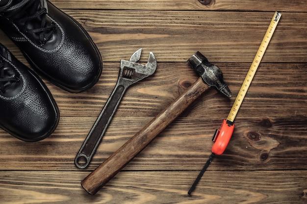 Composición plana con diferentes herramientas e instrumentos de trabajo industrial, equipos de seguridad sobre fondo de madera. vista superior