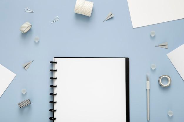 Composición plana de elementos de escritorio sobre fondo azul.