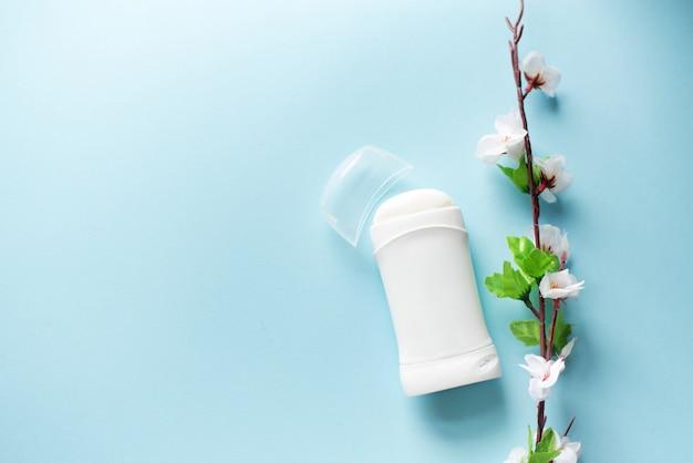 Composición plana de la endecha con el desodorante y las flores en fondo azul. copia espacio