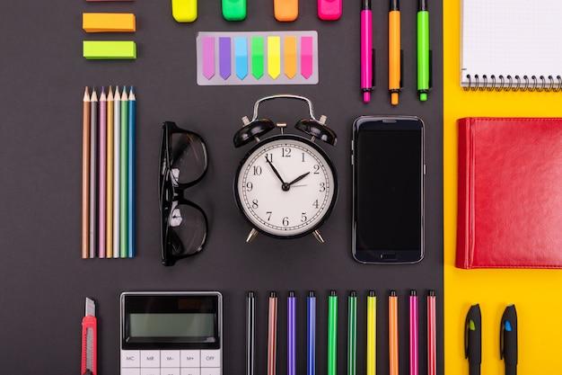 Composición plana de escritorio de negocios con reloj despertador, teléfono inteligente, cuaderno, pegatinas y bolígrafos de colores en negro y amarillo