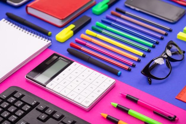 Composición plana de escritorio de negocios con teclado, calculadora, pegatinas y bolígrafos sobre fondo rosa y azul