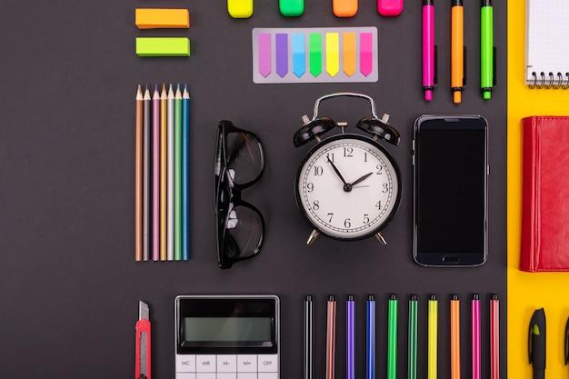 Composición plana de escritorio de negocios con teléfono inteligente, gafas, pegatinas y bolígrafos de colores con copyspace en negro y amarillo