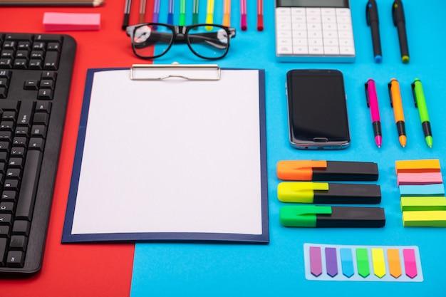 Composición plana de escritorio de negocios con teléfono inteligente, portapapeles, pegatinas y bolígrafo en colores azul y rojo