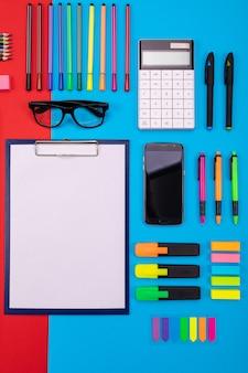 Composición plana de escritorio de negocios con teléfono inteligente, portapapeles, pegatinas y bolígrafo
