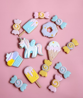 Composición plana con galletas de jengibre glaseadas brillantes sobre fondo rosa.