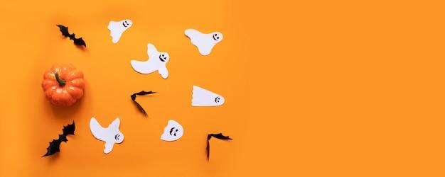 Composición plana de halloween de calabaza naranja, murciélagos negros, moldes de papel blanco para texto