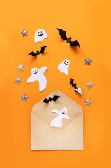 Composición plana de halloween, sobre papel de balsa y murciélagos de papel negro.