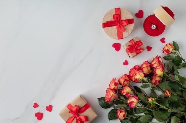Composición plana con hermosas flores, cajas de regalo y anillo de compromiso en la mesa de mármol