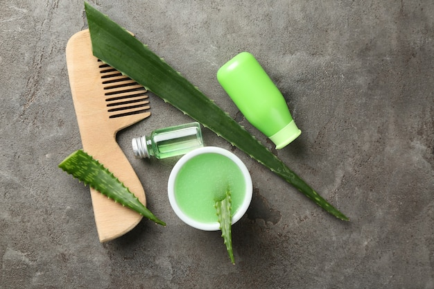 Composición plana con hojas de aloe y cosmética natural para el cabello en la mesa gris