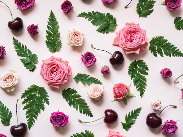 Composición plana de hojas de helecho verde, cerezas y rosas de diferentes tamaños y colores.