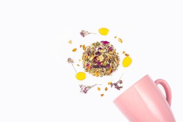 Composición plana laico de té seco disperso de la taza rosa sobre un fondo blanco, copia espacio para el texto. hierbas orgánicas, té asiático verde para la ceremonia del té.