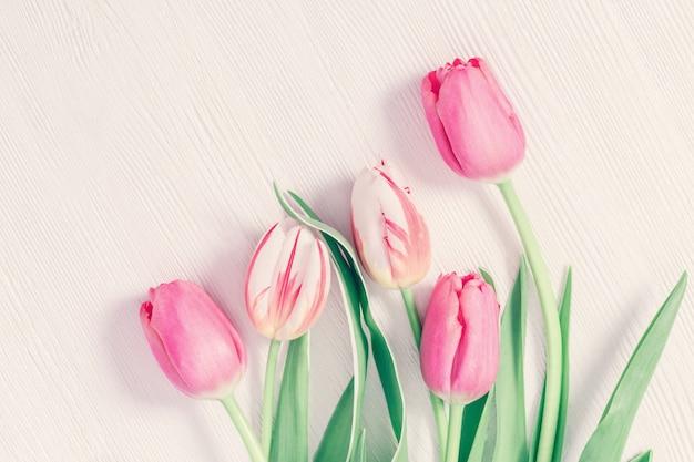 Composición plana laico con tulipanes blancos y rosados en la mesa de superficie de madera. fondo de flores de primavera con espacio de copia para el día de la mujer o la mujer.