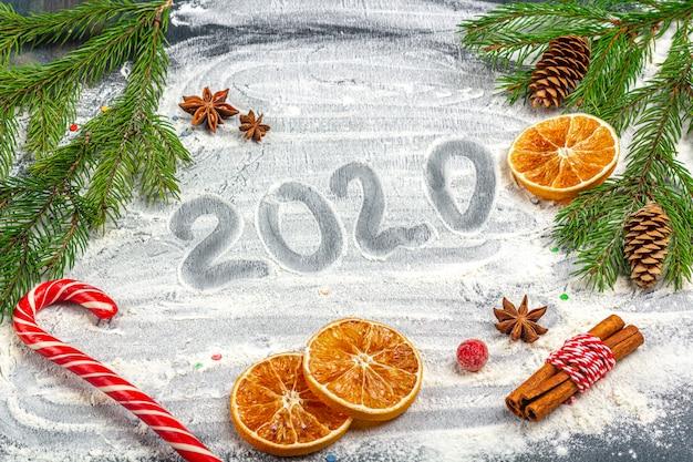 Composición plana de navidad. inscripción 2020 y marco de ramas de abeto, conos, anís estrellado, canela y naranjas secas sobre un fondo de harina.