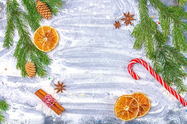 Composición plana de navidad. marco de ramas de abeto, conos, anís estrellado, canela y naranjas secas sobre un fondo de harina.