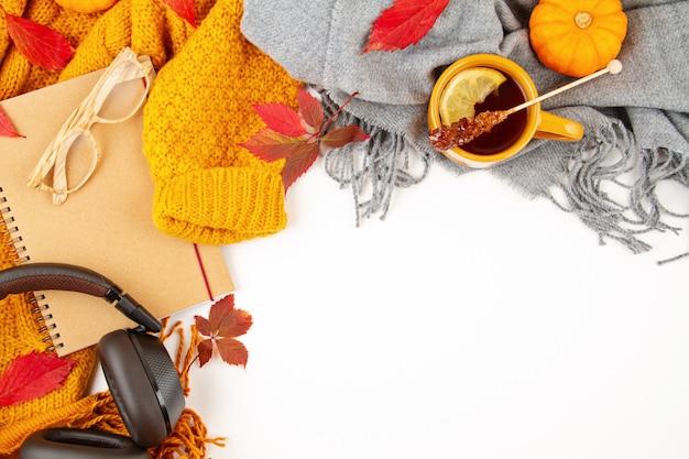 Composición plana de otoño con hojas de otoño, una taza de té caliente y un cálido suéter naranja de lana
