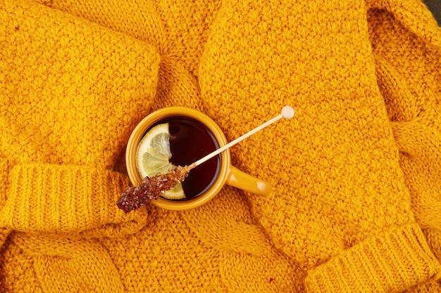 Composición plana de otoño con té y un cálido suéter de lana.