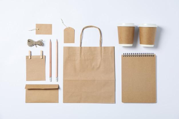 Composición plana con papelería en blanco, vasos de papel y bolsa sobre fondo blanco.