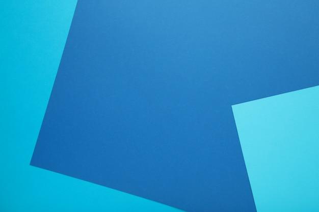 Composición plana de papeles de color azul claro y azul oscuro.