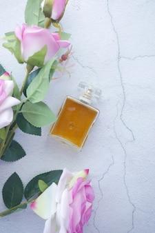 Composición plana de perfume y flor rosa rosa sobre fondo blanco.