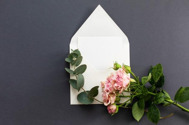 Composición plana con un sobre blanco, una tarjeta en blanco y una flor rosa peonía sobre un fondo gris. maqueta para boda o día de san valentín. vista superior.