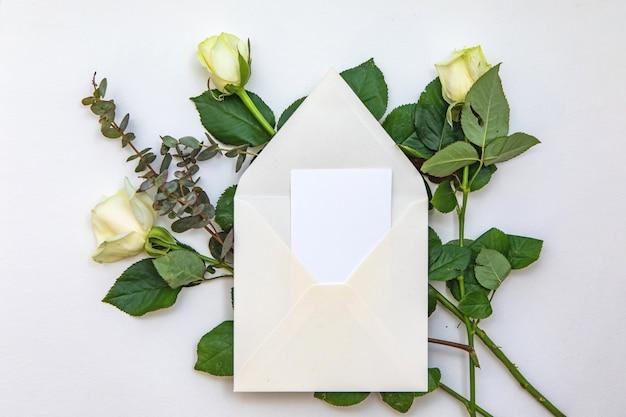 Composición plana con un sobre blanco, una tarjeta en blanco y una rosa flores. maqueta para boda o nota de san valentín. vista superior.