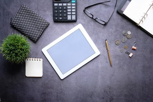 Composición plana de tableta digital y oficina estacionaria sobre fondo negro