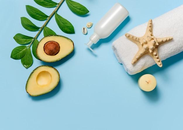 Composición plana con toalla blanca, aguacate, estrella de mar, rama de planta y tubo con aceite de masaje aislado en una pared azul. concepto de spa con espacio para texto.