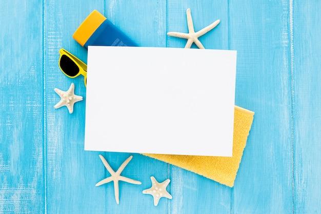 Composición plana para verano con botella de crema de estrellas de mar, gafas, toalla y cartón en blanco