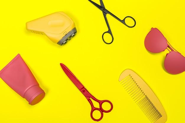 Composición en plano con herramientas de peluquería profesional sobre fondo de color.